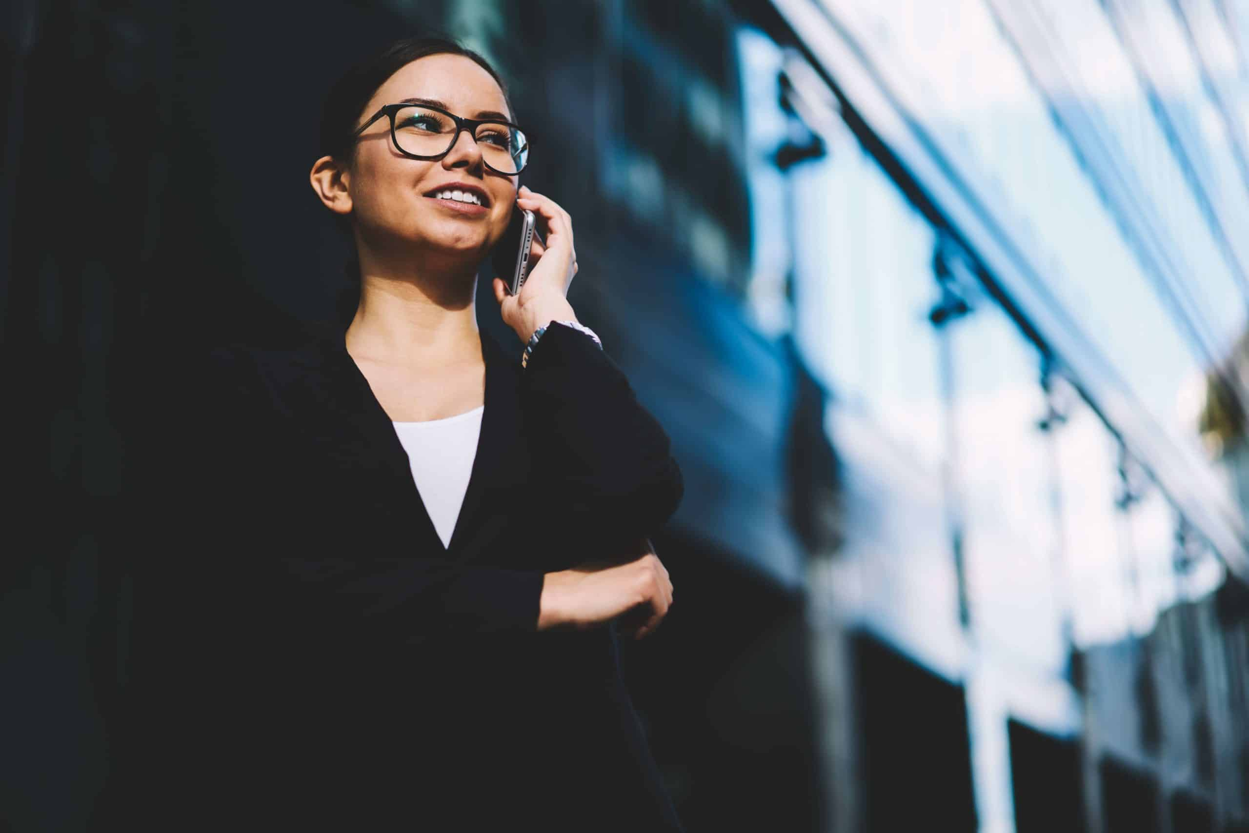 Prosperous businesswoman in eyeglasses and stylish black suit smiling during mobile conversation on modern smartphone standing outdoors near office building.Copy space area for financial information
